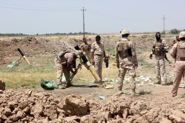 Members of the Iraqi security forces prepare to fire mortar bombs during clashes with Sunni militant group ISIL in Muqdadiyah in Diyala province