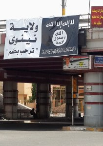 A man sits under a sign with flag belonging to the Islamic State in Iraq and the Levant in Mosul