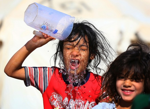 A girl, who fled from violence in Mosul, washes her head at a camp on the outskirts of Arbil