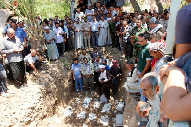 Mourners pray during a funeral in Kirkuk
