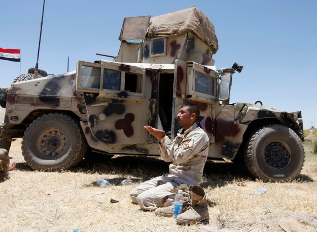A member of the Iraqi security forces prays during an intensive security deployment west of Baghdad