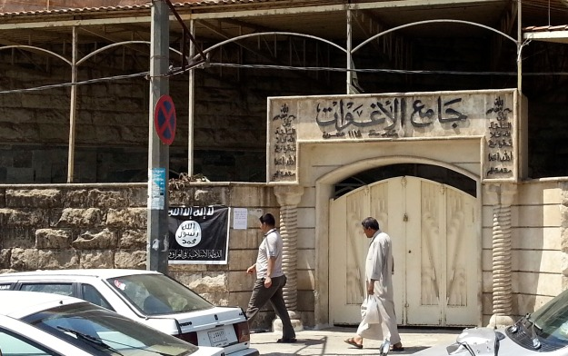 People walk past a banner belonging to the ISIL in Mosul