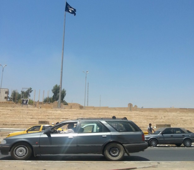 Vehicles drive near a flag belonging to the Islamic State in Iraq and the Levant (ISIL) along a street in the city of Mosul