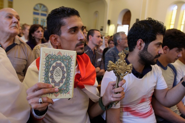 An Iraqi man carrying a cross and a Koran attends a mass at Mar Girgis Church in Baghdad