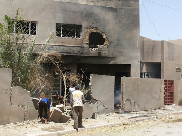People gather near a house after a bomb attack in Fallujah, west of Baghdad