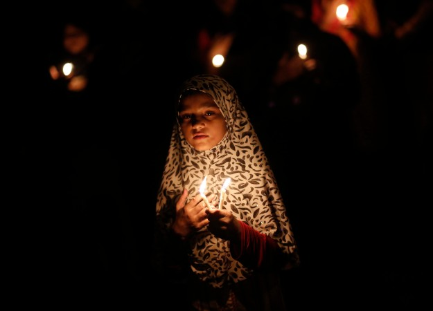 A Shi'ite Muslim girl takes part in a candlelight protest against the ongoing conflict in Iraq, in New Delhi