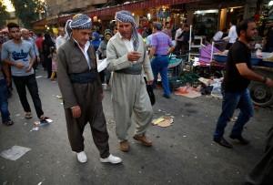 Iraqi Kurdish men walk at a market in Arbil