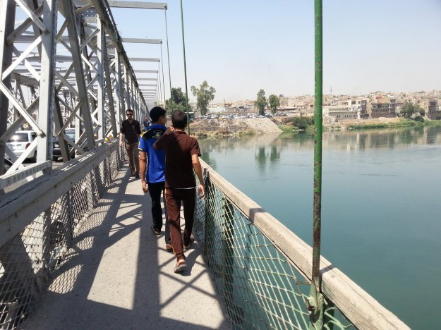 Residents walk on a bridge in the city of Mosul
