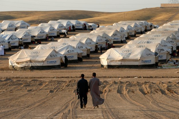 Iraqi refugees, who fled from the violence in Mosul, walk inside the Khazer refugee camp