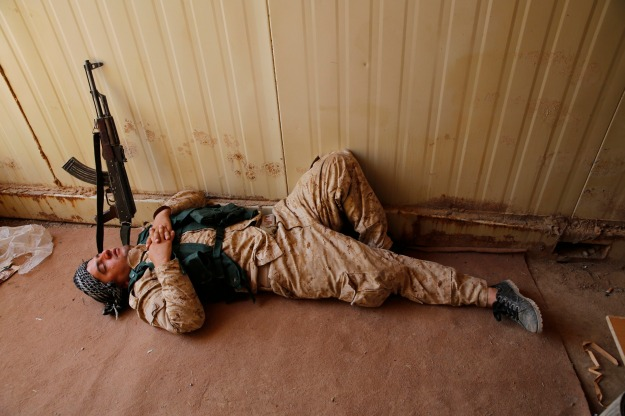 A member of Kurdish security forces sleeps after clashes with militants of the ISIL Basheer
