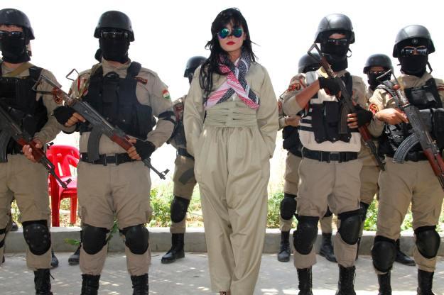 Kurdish pop star Helly Luv poses alongside Kurdish Peshmerga troops at a base in Dohuk