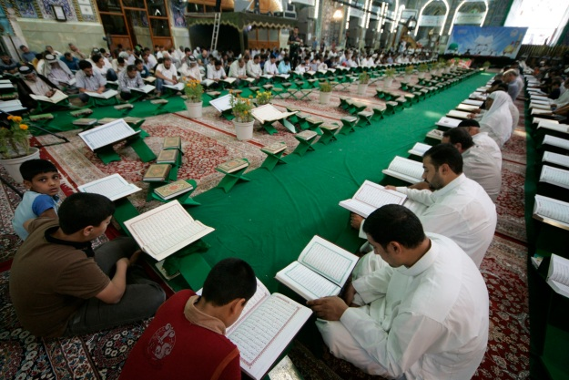 Men read the Koran at the Imam Hussein shrine during the Muslim holy fasting month of Ramadan in Kerbala