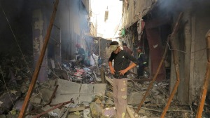 Residents and firefighters inspect market destroyed after attack by Iraq security forces helicopters in Ramadi