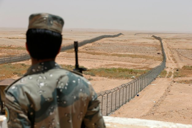 Member of the Saudi border guards force stands guard next to a fence on Saudi Arabia's northern borderline with Iraq