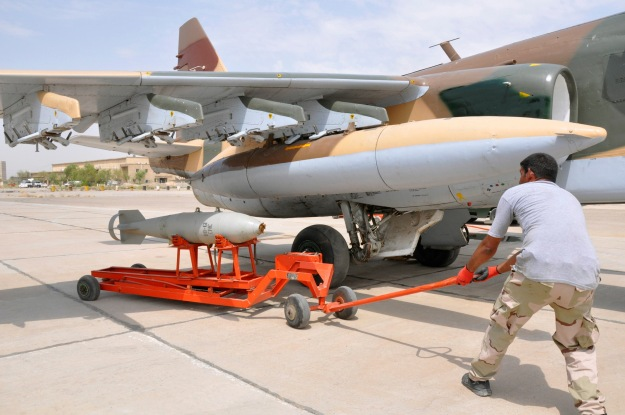 An Iraqi soldier prepares to load a missile onto a Russian Sukhoi SU-25 plane on the tarmac at the al-Muthanna Iraqi military base in Baghdad airport in Baghdad