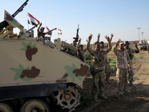 Members of Iraqi security forces gesture during an intensive security deployment on outskirts of Samarra