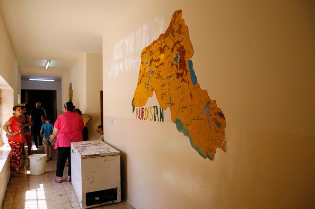 A map of the Kurdistan region is seen on the wall of a school where a Christian family who fled from the violence in Mosul two days ago, is staying in Arbil