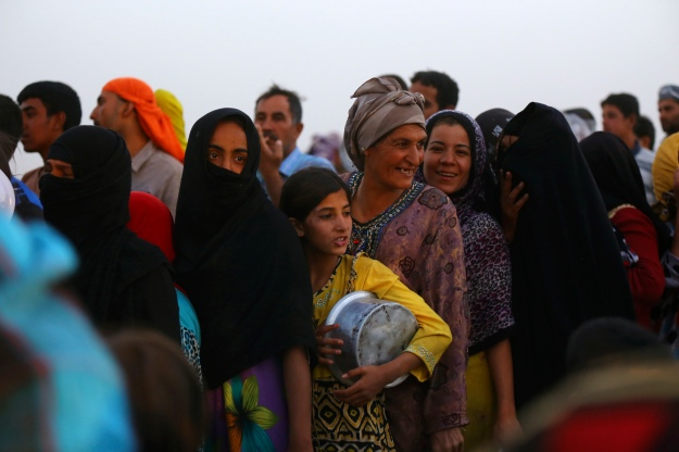 Iraqi refugees, who fled from the violence in Mosul, line up to receive free food during Ramadan inside the Khazer refugee camp