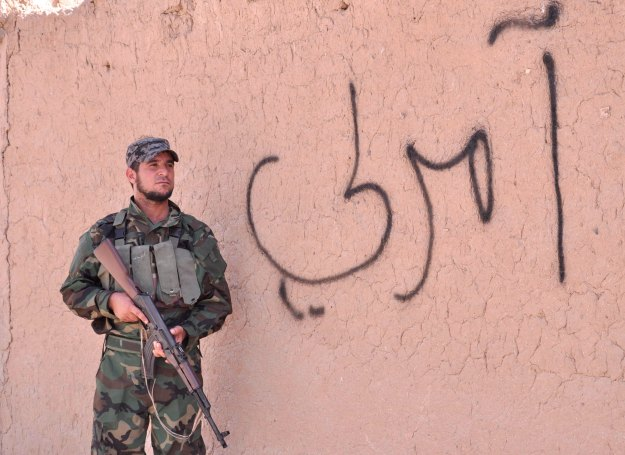 An Iraqi Shi'ite militia fighter takes his position next to a wall in Amerli