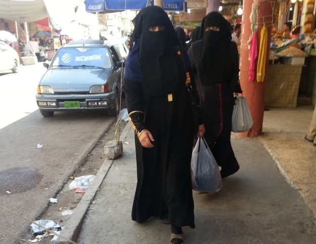 Veiled Iraqi women walk along a street in the city of Mosul
