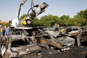 The burnt shell of a car is lifted onto a lorry by traffic police clearing wreckages caused by a triple bombing in a Shi'ite neighbourhood of New Baghdad