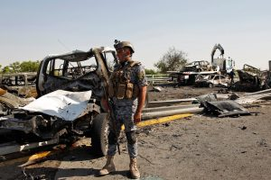 A member of the Iraqi security forces looks at the burnt shells of vehicles after a triple explosion in a Shi'ite neighbourhood of New Baghdad