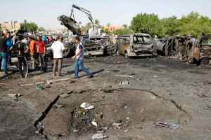 Men stand at the site of three explosions in the New Baghdad neighbourhood