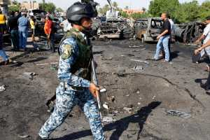 Iraqi security forces inspect the site of three explosions in the New Baghdad neighbourhood