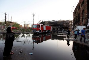 Woman looks at the site of a car bomb attack in Baghdad