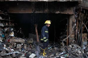 Fire-fighter walks at the site of a car bomb attack in Baghdad