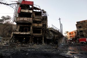 Fire-fighters inspect the site of a car bomb attack in Baghdad