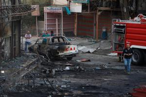 People inspect the site of a car bomb attack in Baghdad