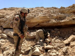 Iraqi soldier looks at the body of an Islamic State militant who was killed by U.S. air strikes on the outskirt of Haditha