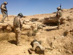 Iraqi soldiers look at bodies of Islamic State militants who were killed by U.S. air strikes on the outskirt of Haditha