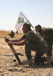Members of the Mehdi Army fire a mortar at Islamic State militants' positions outside the city of Tikrit