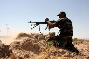 An armed Shi'ite volunteer from the Mehdi Army clashes with Islamic State militants outside the city of Tikrit