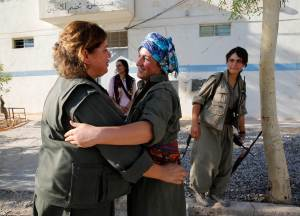 Female members of the PKK hug each other after returning from fighting on the front line against Islamic state militants, in Makhmur
