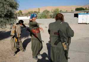 Female members of the PKK walk at their camp, near the frontline of the fight against Islamic State militants, in Makhmur