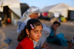 A displaced Iraqi child, who fled from Islamic Sate violence in Mosul, sits with her family outside their tent at Baherka refugee camp