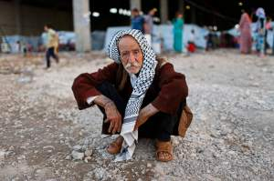 A displaced Iraqi, who fled from Islamic Sate violence in Mosul, squats at Baherka refugee camp in Erbil