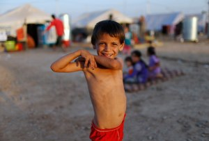 A displaced Iraqi child, who fled from Islamic Sate violence in Mosul, poses for the camera at Baherka refugee camp in Erbil