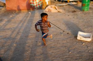 A displaced Iraqi child, who fled from Islamic Sate violence in Mosul, plays at Baherka refugee camp in Erbil
