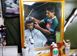 A displaced Iraqi youth, who fled from Islamic Sate violence in Mosul, gets a haircut in Baherka refugee camp in Erbil