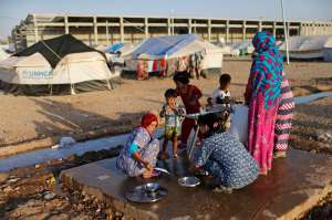 Displaced Iraqis who fled from Islamic Sate violence in Mosul, wash dishes at Baherka refugee camp in Erbil