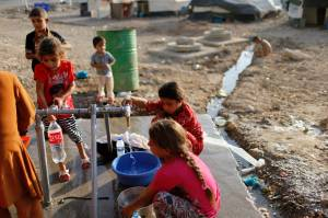 Displaced Iraqis, who fled from Islamic State violence in Mosul, get water at Baherka refugee camp in Erbil