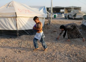 A displaced Iraqi boy, who fled from Islamic State violence in Mosul, carries his brother at Baherka refugee camp in Erbil