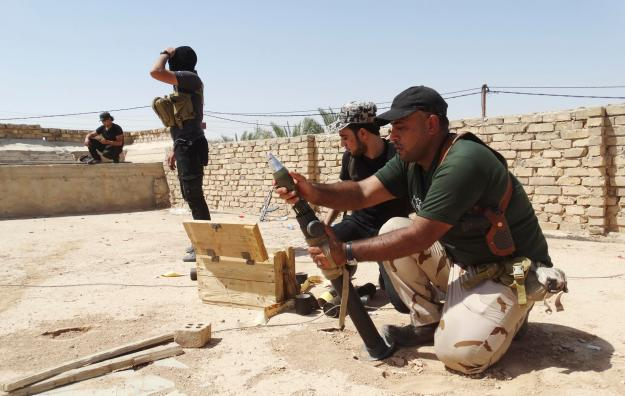 Members of Iraqi security forces and tribal fighters prepare a mortar launcher during a fight with Islamic State militants on the outskirts of Ramadi