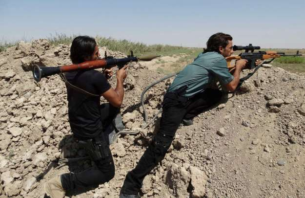 Tribal fighter forces carry weapons during a fight with Islamic State militants on the outskirt of Ramadi