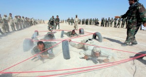 Shi'ite fighters, who have joined the Iraqi army to fight against militants of the Islamic State, formerly known as the Islamic State of Iraq and the Levant (ISIL), take part in field training in the desert in the province of Najaf
