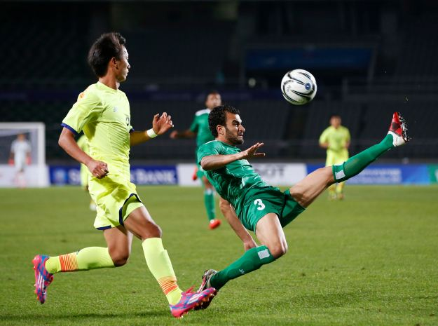 Iraq's Ali Bahjat Fadhil challenges Japan's Sei Muroya during their men's soccer qualifier match at Goyang Stadium in Goyang, for the 17th Asian Games in Incheon
